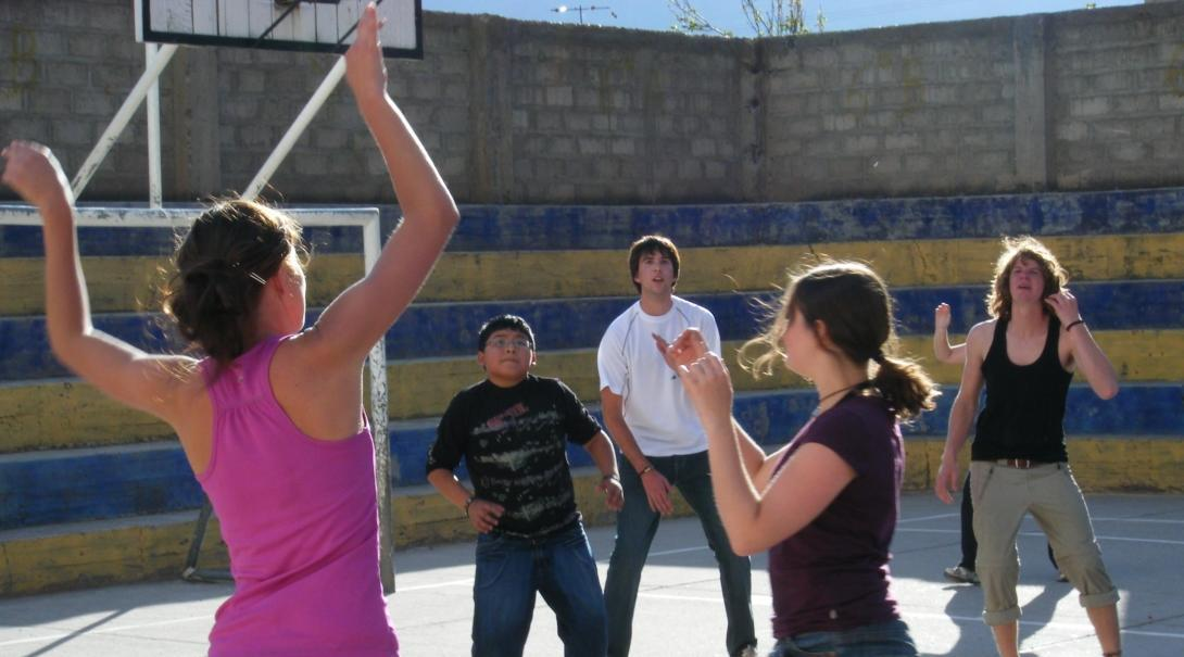 A volunteer coaching sports in schools in Peru demonstrates for her team